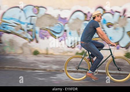 Hipster man riding bicycle on road along urban graffiti wall - Stock Photo