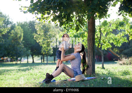 Young mother raising baby on hands up in the air - Stock Photo