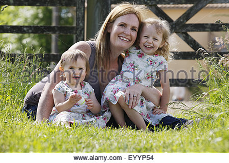 Portrait of mother and daughters sitting on grass in wildflower meadow smiling at camera - Stock Photo