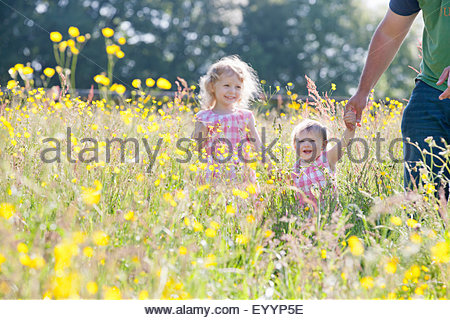 Portrait of smiling baby and young girl daughters holding fathers hand in wildflower meadow - Stock Photo