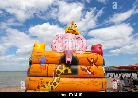 Colourful animals on an inflatable bouncy castle at the seaside - Stock Photo