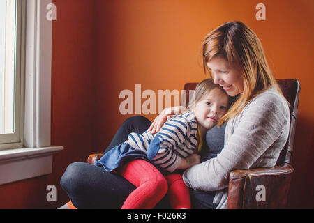 Mother and daughter sitting in a chair together - Stock Photo