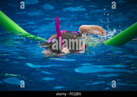 A girl swimming in a pool with goggles and a snorkel - Stock Photo