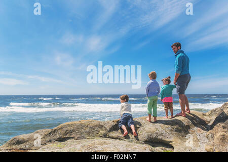 Father and three children on the beach - Stock Photo