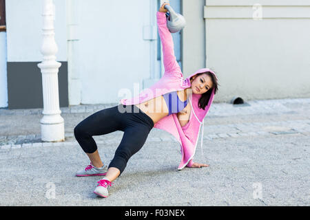 Athletic woman exercising turkish get up with kettlebell - Stock Photo