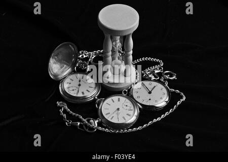 Watches and hourglass on black velvet. - Stock Photo