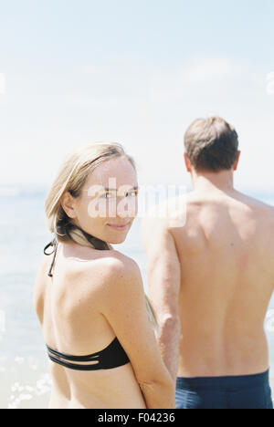 Couple in swimwear by the ocean, woman smiling at camera. - Stock Photo