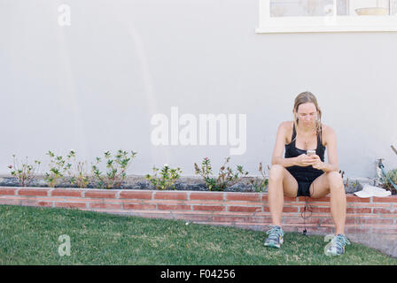 Blond woman in sportswear sitting on a garden wall, resting after a jog. - Stock Photo