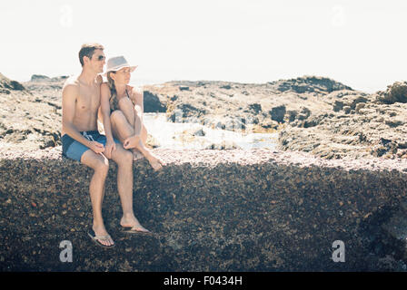 A man and woman, couple on the beach sitting on a wall by a rock pool. - Stock Photo