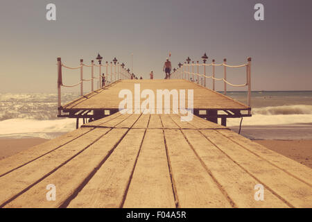 Old wooden pier over the sea shore, tinted photo - Stock Photo