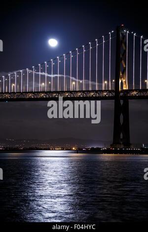 San Francisco-Oakland Bay Bridge at night with the moon - Stock Photo