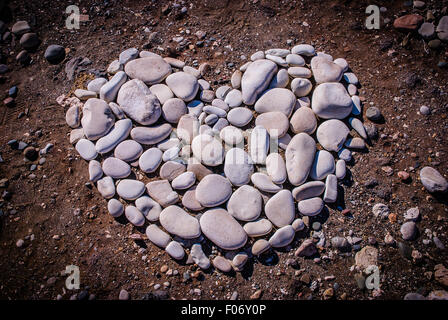 Heart shaped design made from pebbles on the beach - Stock Photo