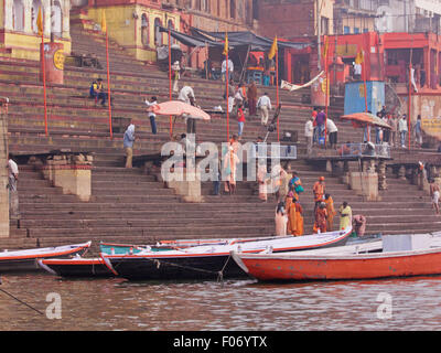 Hindu pilgrims bathing in the early morning at Dasawamedh ghat beside the sacred river Ganges at Varanasi - Stock Photo