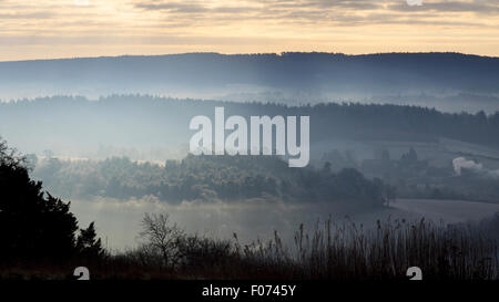 Low morning winter sun rises over the misty landscape as viewed from Newlands Corner, Guildford, Surrey - Stock Photo
