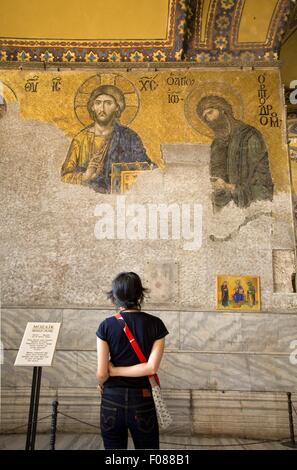 Rear view of woman looking at mosaic of Jesus on wall in Hagia Sophia, Istanbul, Turkey - Stock Photo