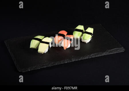 Vegetable sushi on flat slate, black background - Stock Photo