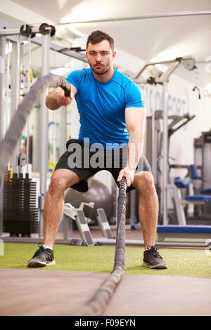 Young man working out with battle ropes at a gym, vertical - Stock Photo