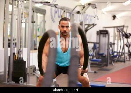 Young man working out with battle ropes at a gym - Stock Photo