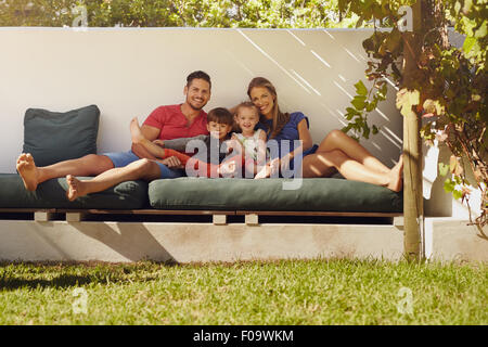 Portrait of happy young family sitting on patio smiling at camera. Couple with kids sitting on couch in their backyard. - Stock Photo