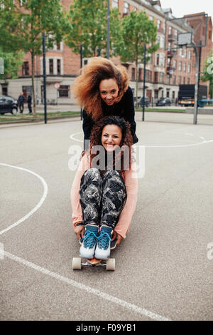 Hipster girls riding on skateboards along the road. Two young women skating. Woman pushing her friend on longboard. - Stock Photo
