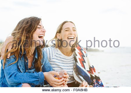 Two young female friends laughing on beach - Stockfoto