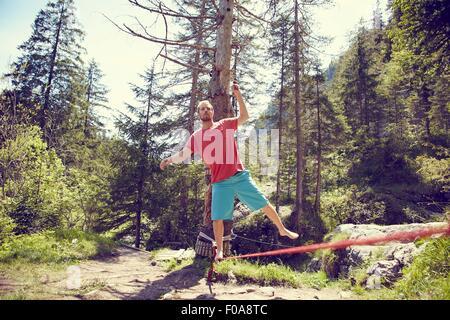 Man balancing on rope, Ehrwald, Tyrol, Austria - Stock Photo