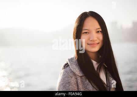 Portrait of young woman with long brunette hair in centre parting looking at camera smiling - Stock Photo
