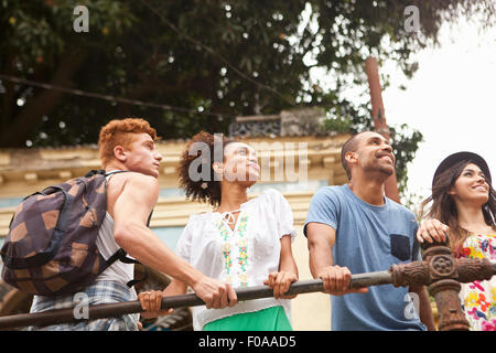 Small group of friends holding onto railing, smiling, low angle view - Stock Photo