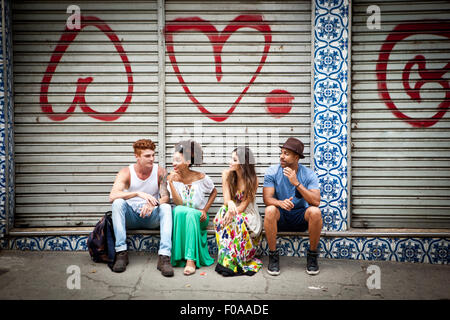 Group of friends, sitting on ledge, talking - Stockfoto