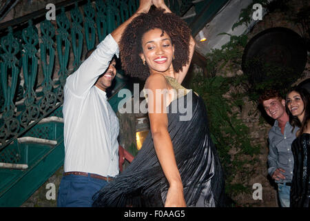Couple dancing outdoors, friends looking on - Stock Photo