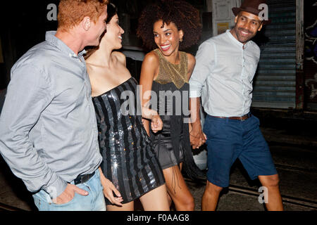 Four friends walking along street together at night - Stock Photo