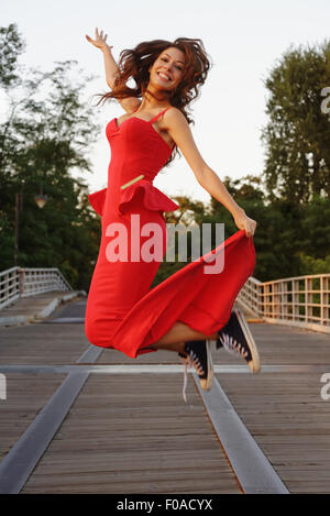 Portrait of a young woman in a smart red dress and baseball shoes jumping in motion - Stock Photo