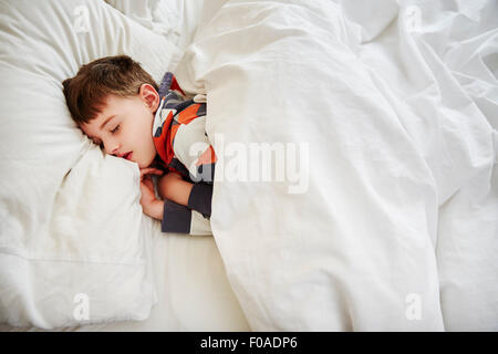 Young boy sleeping in bed - Stock Photo