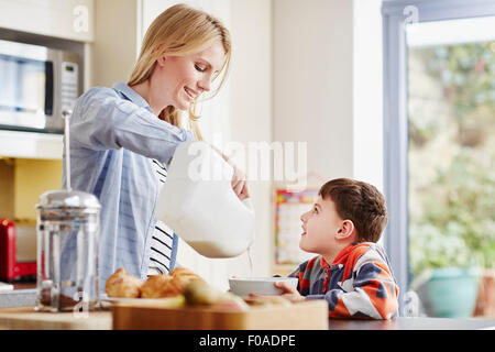 Mother pouring milk into son's breakfast bowl - Stock Photo