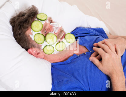 man in bed with facial and smiling - Stockfoto