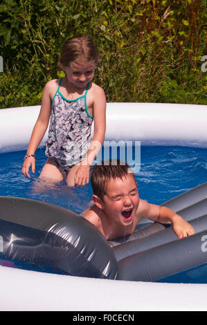 2 Children Cooling Off During Hot Summers Day - Stock Photo