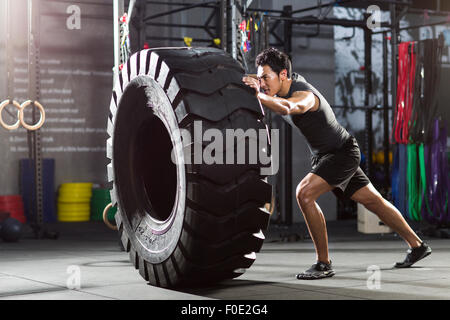 Young man pushing large tire in crossfit gym - Stock Photo