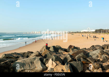 Many unknown fishermen on Blue Lagoon beach against Durban city skyline in South Africa - Stock Photo