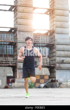 Young jogger running outdoors - Stock Photo