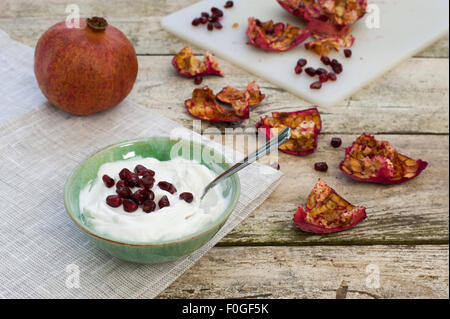 Healthy snack a bowl of yogurt and pomegranate seeds. A whole fruit ...