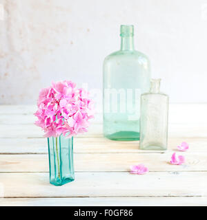 a pink hydrangea flower head in a turquoise vintage glass bottle, with two more glass bottles in the background - Stock Photo