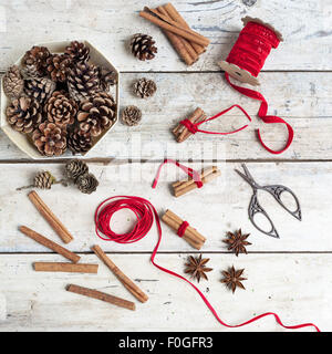 pinecones, spices and cinnamon bundles tied with red ribbon for Christmas - Stock Photo