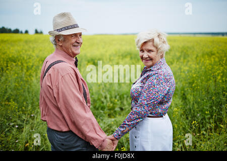 Happy seniors holding by hands in the field - Stock Photo