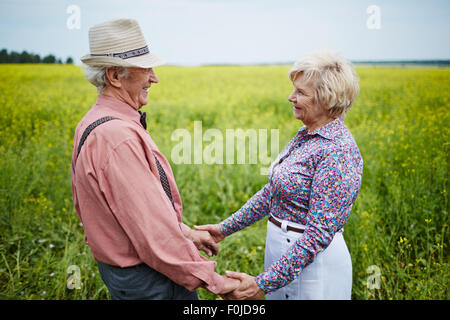 Romantic seniors holding by hands and looking at one another in the field - Stock Photo