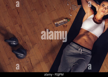Top view of fitness model lying on exercise mat. Overhead shot of fitness instructor tired resting on mat with water - Stock Photo