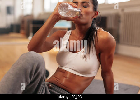Fitness woman drinking water from bottle. Muscular young female at gym taking a break from workout. - Stock Photo