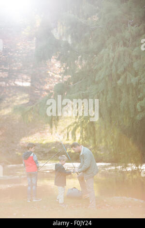 Father and sons preparing fishing rods in woods - Stock Photo