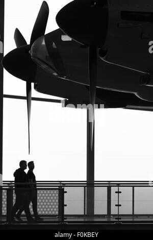 Two visitors at the imperial war museum, Duxford, walk past a de Havilland Mosquito that hangs from the roof of - Stock Photo