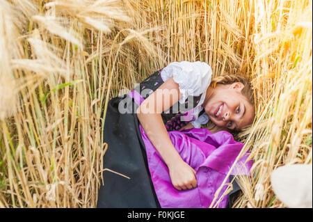 Germany, Saxony, portrait of smiling girl lying in a grain field wearing dirndl - Stock Photo