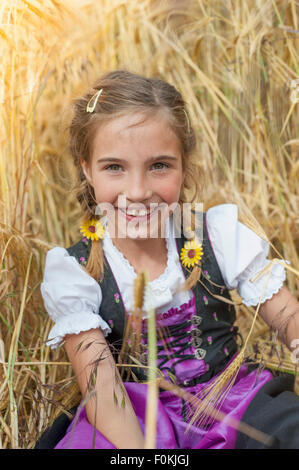 Germany, Saxony, portrait of smiling girl sitting in a field wearing dirndl - Stock Photo